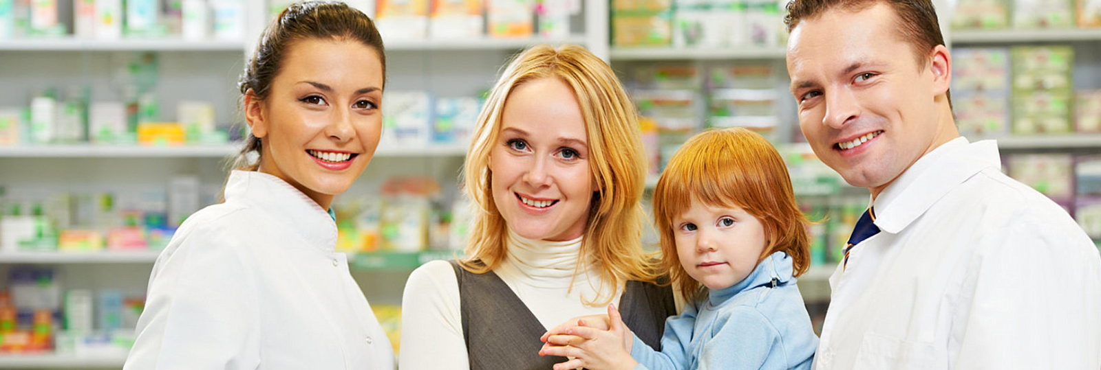 a mother carrying her child with two smiling pharmacists